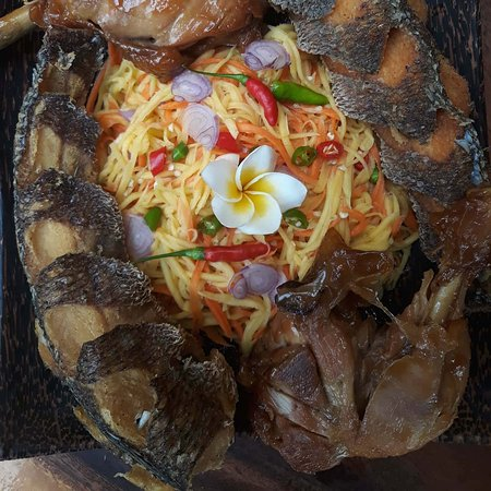 Fried fish and boiled chicken over green mango spicey salad.