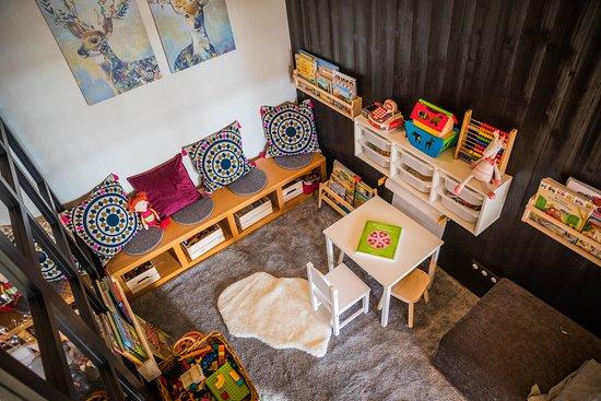 Chieming, Nemecko: Die gemütliche Kinderecke lädt die Kleinsten zum Spielen ein. Hier kann in Wohnzimmer-Atmosphäre gelesen, gebaut, gespielt oder gemalt werden.