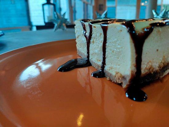 Cheesecake estilo NY con jarabe de chocolate.