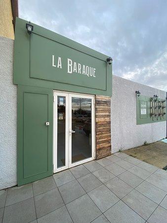 La devanture du restaurant, dans des tons de gris et de vert.