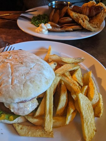 Chicken burger and chips, with chef's special of turkey schnitzel in background.