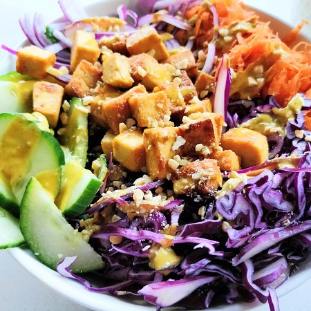 Our Thai Salad featuring kale, sliced cucumber, shredded carrot and cabbage, red onion, grilled tofu, and peanuts with a spicy peanut dressing.