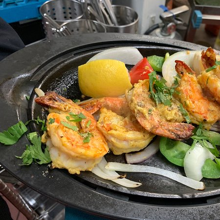 Tiger Shrimp, prepared in the Tandoor, charcoal fired clay oven . Served with grilled onions and Bell Peppers