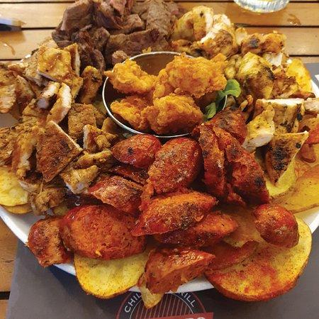 Picada Super Bro para compartir entre amigos, tiene chorizo, pollo, lomo, cerdo y camarones sobre una cama de papas fritas.