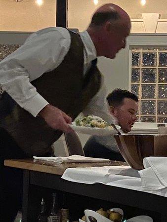 Waiter prepares Caeser salad tableside