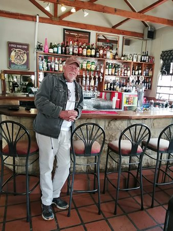 Tony. The owner of The Red Rooster Restaurant, Wakkerstroom standing in front of his pub.