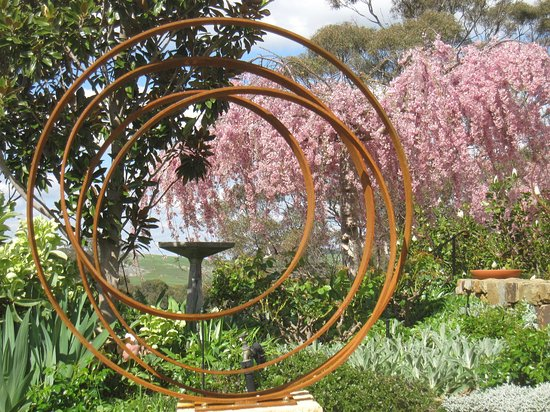 "Mica Grange Garden: ""Ribbons"" by Manning Sculptures, with weeping cherry tree in the background"