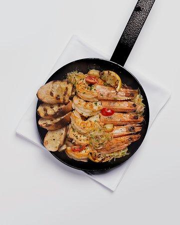Camarões a la plancha. Camarões na brasa servidos em frigideira de ferro, com alho assado e vinagrete de alho poró defumado. Acompanha pães de fermentação natural.