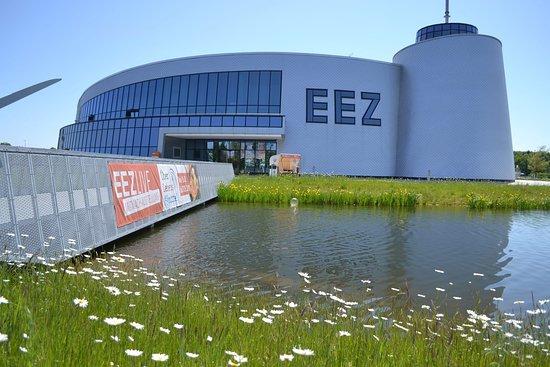Aurich, Almanya: Direkt am See gelegen führt eine Besucherbrücke auf die künstlich angelegte Insel. 4 Bauteile fügen sich harmonisch über Bögen, Kreise und Ellipsen zum Gesamtbauwerk des Energie-Erlebnis-Zentrums zusammen.