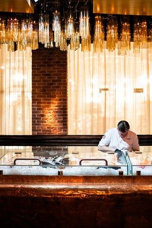 В центре ресторанного зала установлен оббитый медью прилавок, напоминающий всплывающую из морских глубин подводную лодку. В ледяных боксах здесь выложены креветки, устрицы и рыба, а повара сервируют быстрые блюда.
