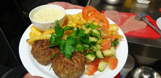 French fries, meat cutlets, vegetables, and sauce