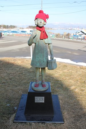 赤い帽子とマフラーが着せられた少女像