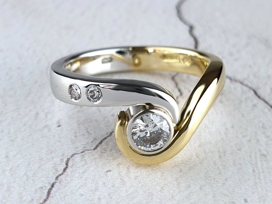 A bespoke Hug engagement ring in platinum and gold with diamonds.