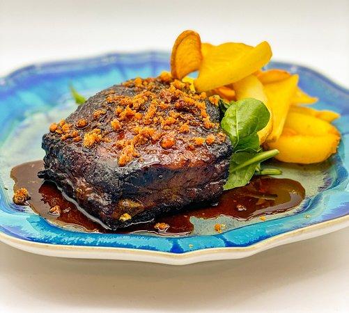 Costilla de cerdo a baja temperatura en su jugo con cebolla frita. Acompañado de patatas dipper, rúcula y tomate.