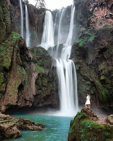 "Ouzoud Waterfalls are located near the Moyen Atlas village of Tanaghmeilt, in the province of Azilal, 150 km northeast of Marrakech, in Morocco. Ouzoud means ""the act of grinding grain"" in Berber. This seems to be confirmed by the frequent mills in the region."