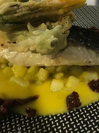 Trancio di spigola con patate allo zafferano pomodori secchi e fiori di zucchina croccanti