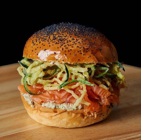 The Salmon Gravlax Bun  Ingredients:  Brioche Bun Dill Gravlax Salmon (24h) Crispy Zucchini Roasted Aubergine & Feta Cream Grainy Mustard Mayo