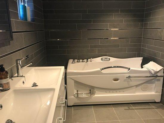 Bathroom with shower and jacuzzi bath. Suite Skuteviken https://www.villalonndal.se/varingra-rum--sviter.html
