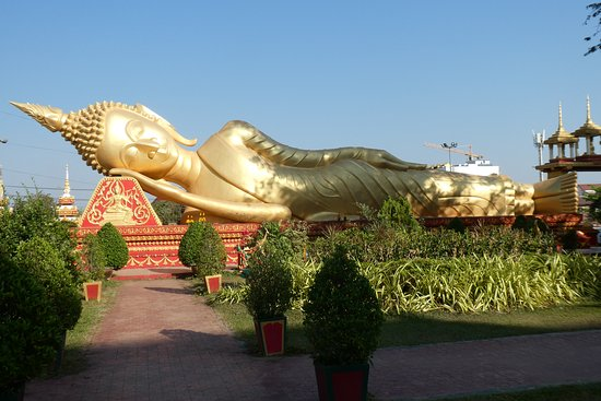 """Another great """"must see"""" feature in the temple complex  is the good sized gold imaged reclining Buddha resting very peacefully around landscaped gardens on an impressive, decorative gold and red painted bed."""