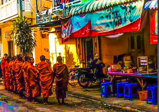 Cambodia: Monks await alms outside a shop in Battambang