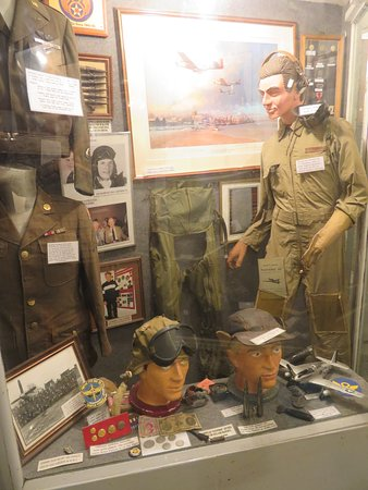 Display cabinet celebrating the Mustang and those who flew them. Note the Mk 111  'Pilot's Notes' hand book in the knee pocket.