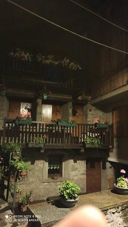 """Luglio 20 - Passeggiando per Etroubles di notte, sotto la pioggia - Inserito tra i Borghi più belli d'Italia, questa perla è incastonata, nel cuore della valle del Gran San Bernardo,tra suggestive vette alpine. Il suo antico centro storico, caratterizzato da un """"intrigo""""di case con balconcini fioriti,stradine acciottolate,e fontanili, ospita un museo a cielo aperto. La tenue illuminazione notturna lo rende ancora più fiabesco..."""
