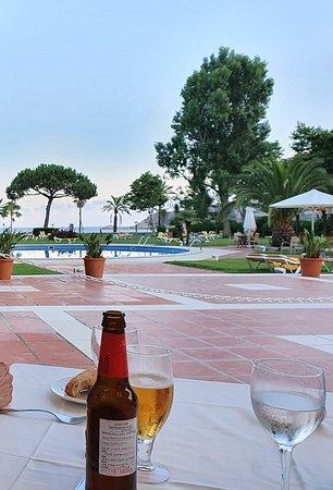 Comedor al aire libre con vistas a la piscina y el mar.