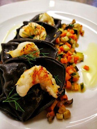 Ravioli ripieni di salmone affumicato su caponatina di verdure e gamberi