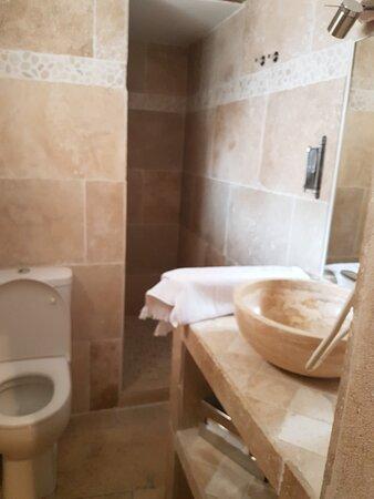 Murs en travertin, la douche est avec mitigeur et avec une pression conséquente.