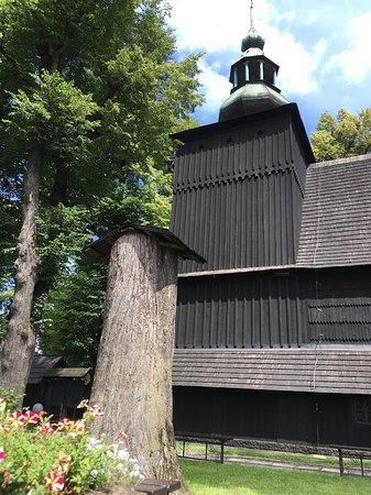 Kapliczka w ściętym drzewie przy drewnianym kościółku