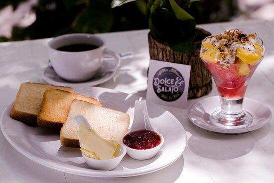 """Desayuno """" Pane e Fruta """" , pan tostado , mantequilla , mermelada  y una copa de frutas de estacion servidas con yogurth y granola. Acompañados de cafe ."""