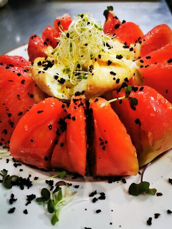 Ensalada de Tomate Rosa con burrata ahumada y tierra de aceitunas del bajo Aragón.