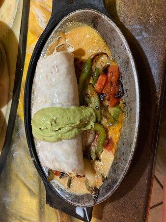 steak burrito, onions, peppers, mushrooms, tomatoes and chorizo on the platter under the burrito!