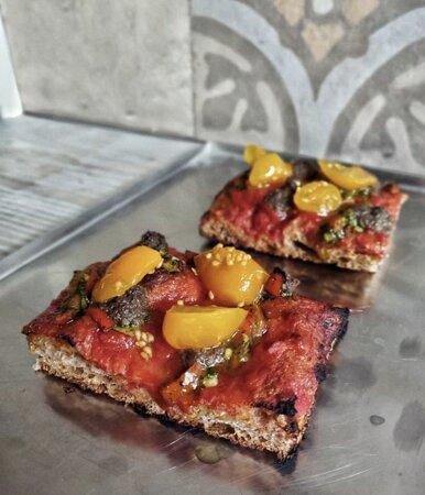 Teglia rossa con pomodoro san marzano dop, tapenade, salsa verde, peproncino e pomodori gialli datterini