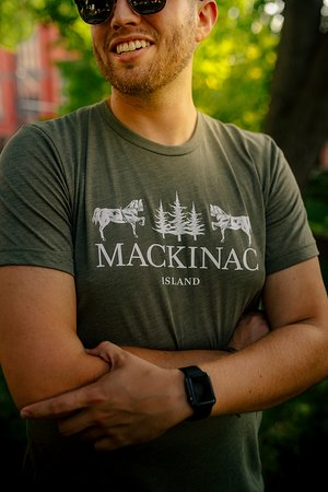 This is our short sleeve T-shirt with signature horse and tree graphic. Our new Signature styles evokes #PureMackinac Island nostalgia. Inspired by woodcut designs from the past, this short-sleeve T-shirt's design embraces the history that makes Mackinac Island what is today.