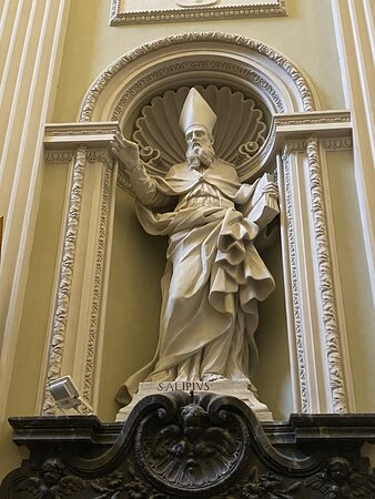 In between the side chapel arches are six statues of saints in arched niches with intricately molded frames. This is St. Alypius of Thagaste (a friend of St Augustine).