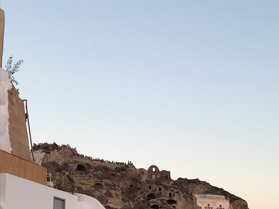 Tourists on the castle of Oia and the boats are assembled to enjoy Oia's sunset 🌅