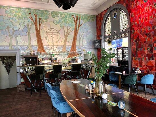 Art deco interieur met rechts de rode muur kunstenares Vika Mitrichenka en achter de bar de muur gemaakt door kunstenaar Christiaan Kattenberg.