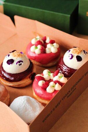 A box of handmade doughnuts. In the box: Raspberry & Vanilla, Panna Cotta & Blueberry, Chocolate Hazelnut Cream, Maple & 'Bacon' (Vegan)