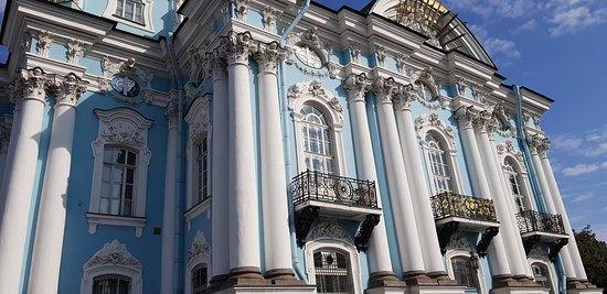 La fachada está pintada de blanco y azul, decorada con columnas y alquitrabes.