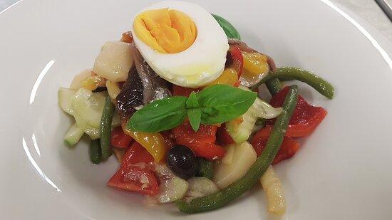 Un'insalata tipica della riviera ligure, galletta del marinaio imbevuta in olio e aceto, verdure di stagione, olive, capperi, filetti di acciuga, basilico e mezzo uovo