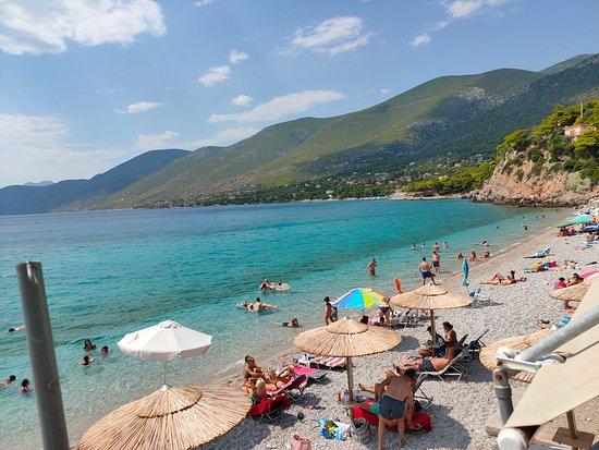 Porto Germeno, Greece: Φωτογραφία της παραλίας κάτω από τα μαγαζιά. Η παραλία έχει βότσαλο και σε ένα μικρό κομμάτι της είναι οργανωμένη με ομπρέλες  και ξαπλώστρες. Η θάλασσα είναι καθαρή και αρκετά ζεστή.