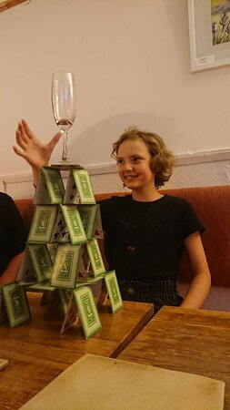 Nancy balancing a champagne glass on a house of cards