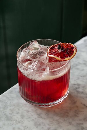 Our house Negroni cocktail made with a mix of hisbiscus infused gin, campari, vermouth and orange zest