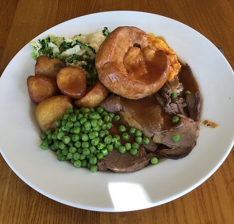 Sunday Roast Beef lunch, with Yorkshire pudding, roast potatoes, cabbage, cauliflower cheese sauce, carrot and turnip, with garden peas,gravy.