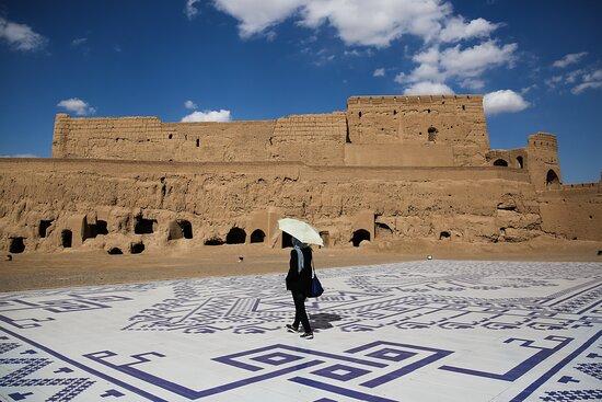 Tourist presence with umbrellas at Narin Castle. Meybod, Yazd, Iran Photo @alivasigh
