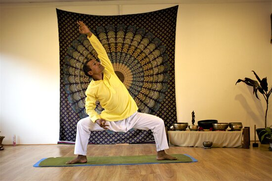 Niru yoga homestay with yoga retreat center's yoga hall teaching yoga class with yogi Rajan Bastola