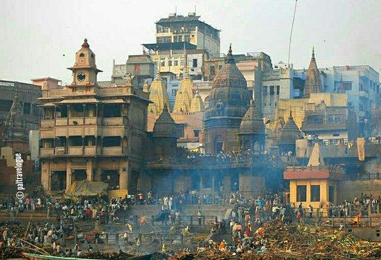 Views of Manikarnika Ghat during morning boat ride over river Ganges .