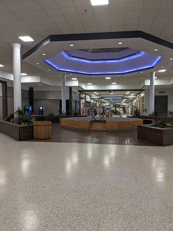 Auburn, ME : The center of the mall. The mall sports purple overhead lighting throughout and deep burgundy brick floors in areas.