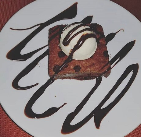 Chocolate brownie infused with chocolate chips and topped with homemade vanilla bean ice cream